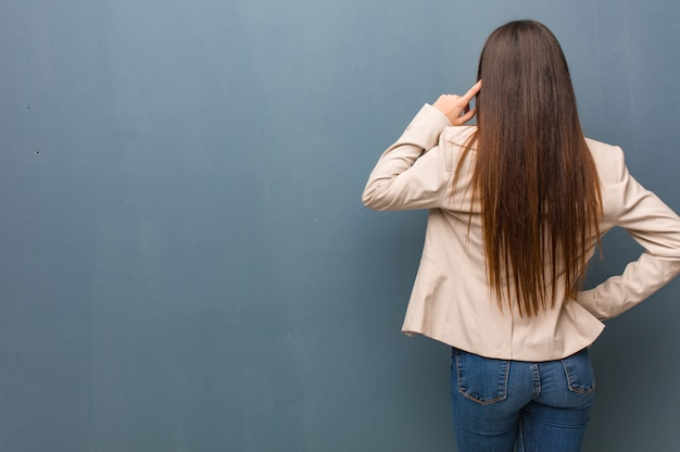 Young business woman from behind thinking about something