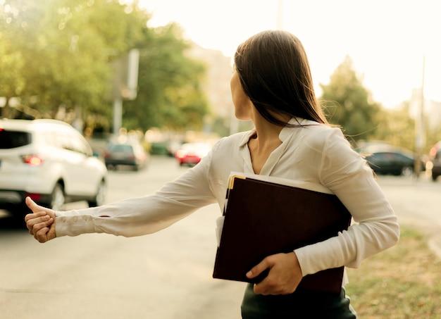 若いビジネスウーマンのジェスチャーは、市内の道路に立っているときに車をキャッチします