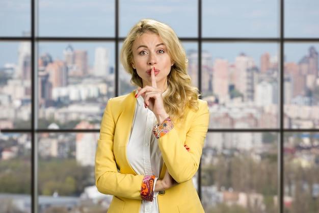 젊은 비즈니스 여자 몸짓 침묵. 비즈니스 센터 창에 침묵 제스처를 만드는 아름 다운 젊은 사무실 매니저.