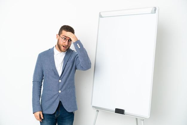 Молодая деловая женщина делает презентацию на белой доске, изолированной на белом фоне, делает неожиданный жест, глядя в сторону