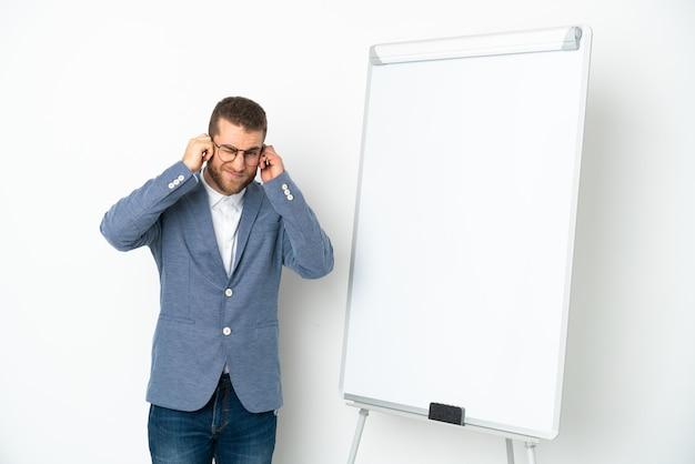 Молодая деловая женщина, проводящая презентацию на белой доске, изолированной на белом фоне, разочарована и закрывает уши