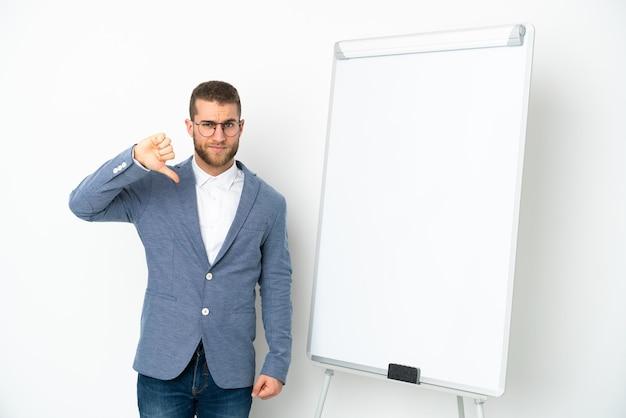 부정적인 표현으로 아래로 엄지 손가락을 보여주는 흰색 배경에 고립 된 화이트 보드에 프레 젠 테이 션을주는 젊은 비즈니스 우먼