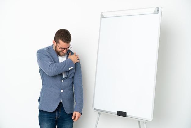 努力したために肩の痛みに苦しんでいる白い背景で隔離のホワイトボードでプレゼンテーションを行う若いビジネスウーマン
