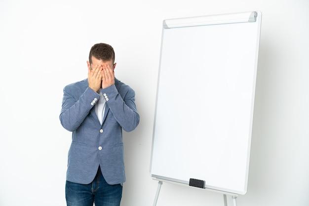 피곤하고 아픈 표정으로 흰색 배경에 고립 된 화이트 보드에 프레젠테이션을 젊은 비즈니스 우먼