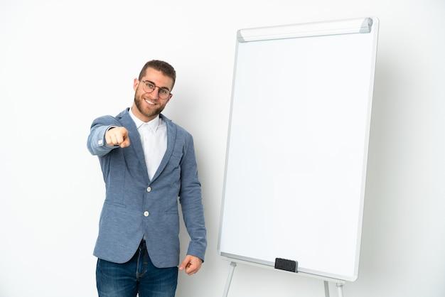 Молодая деловая женщина делает презентацию на белой доске, изолированной на белой стене, указывая вперед с счастливым выражением лица