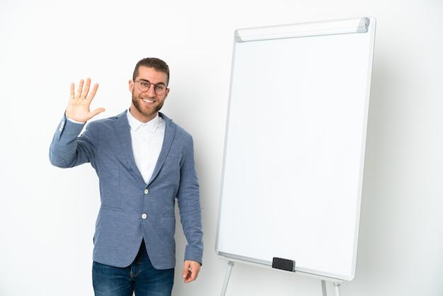 행복 한 표정으로 손으로 경례 흰 벽에 고립 된 화이트 보드에 프레 젠 테이 션을주는 젊은 비즈니스 우먼