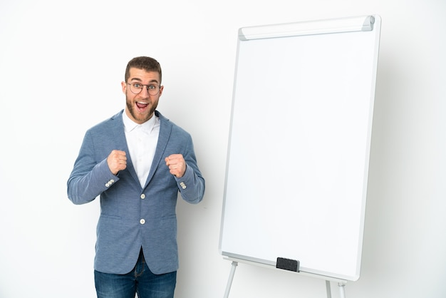 Young business woman giving a presentation on white board isolated on white background celebrating a victory in winner position