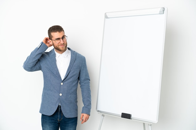 Young business woman giving a presentation on white board isolated on white wall having doubts