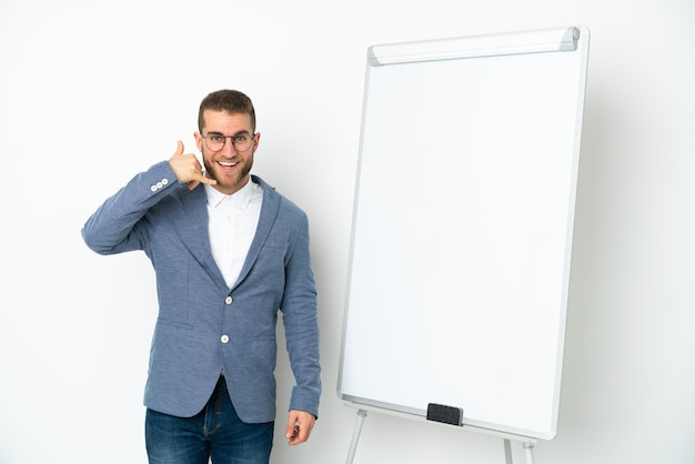 Young business woman giving a presentation on white board isolated on white wall making phone gesture. call me back sign
