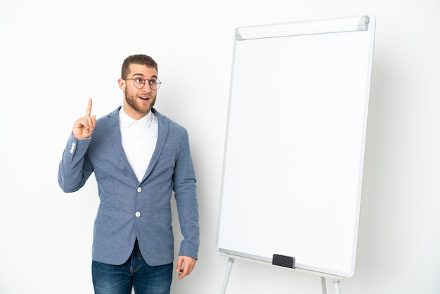 Young business woman giving a presentation on white board isolated on white wall thinking an idea pointing the finger up