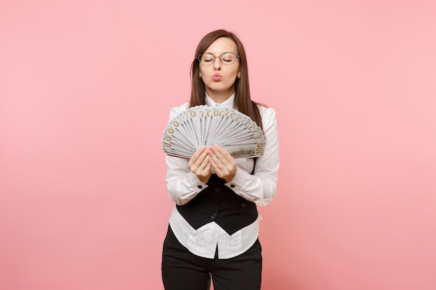 Young business woman in glasses holding bundle lots of dollars, cash money blowing lips kissing isolated on pink background. lady boss. achievement career wealth concept. copy space for advertisement.