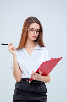 Young business woman in glasses with pen and clipboard
