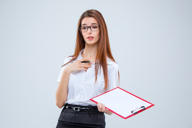 Young business woman in glasses with pen and tablet for notes on a gray background