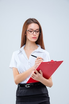 The young business woman in glasses with pen and tablet for notes on a gray