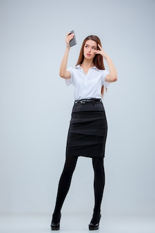 The young business woman on gray wall