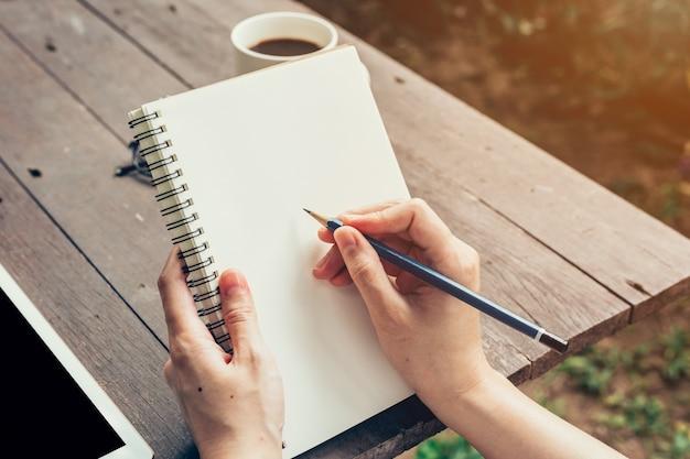 노트북에 쓰는 연필로 젊은 비즈니스 여자 손. 노트북에 작성 하 고 커피 숍에서 일하는 연필로 여자 손.
