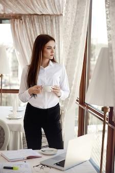若いビジネス女性は彼女の職場でコーヒーブレークを持っています