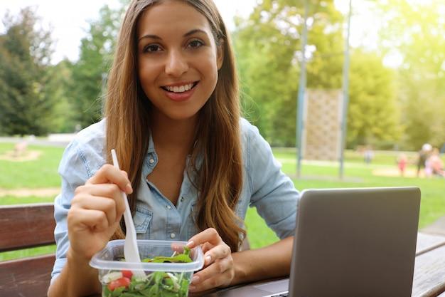 Молодая деловая женщина обедает, сидя в городском парке, глядя на камеру.