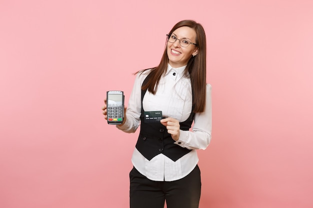 Young business woman hold wireless modern bank payment terminal to process and acquire credit card payments, black card isolated on pink background. lady boss. achievement career wealth. copy space.