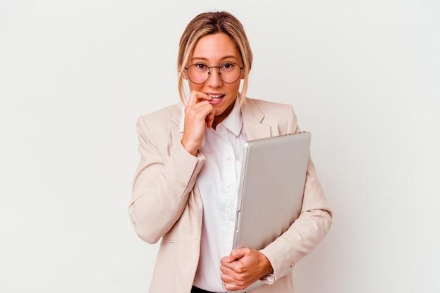 손톱을 물어 뜯는 흰 벽에 고립 된 노트북을 들고 젊은 비즈니스 우먼, 긴장하고 매우 불안
