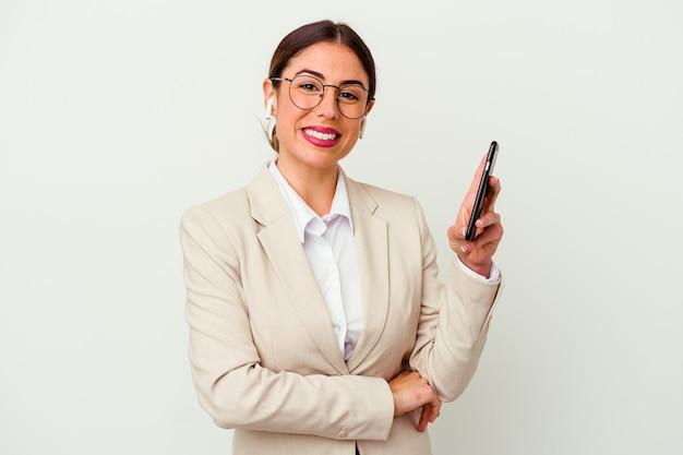 笑って楽しんで白い背景で隔離の携帯電話を保持している若いビジネス女性。