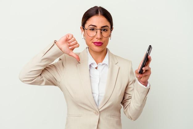 嫌なジェスチャーを示す白い背景に分離された携帯電話を持つ若いビジネス女性は、親指を下に向けます。不一致の概念。