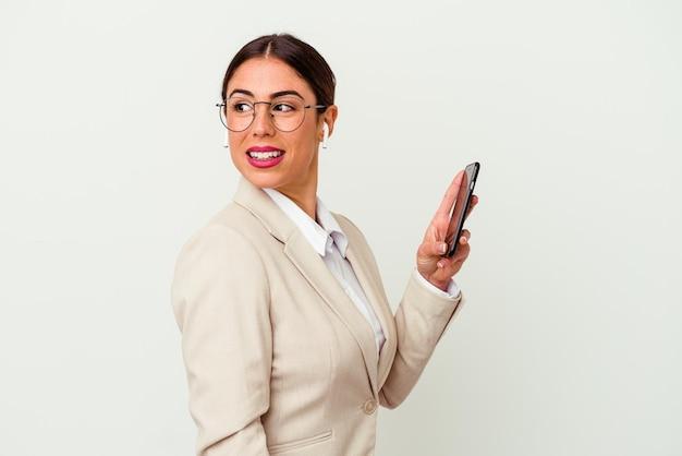 흰색에 고립 된 휴대 전화를 들고 젊은 비즈니스 우먼 옆으로 웃 고, 명랑 하 고 즐거운 보인다.