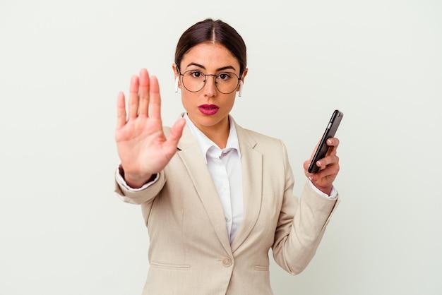一時停止の標識を示す伸ばした手で白い立って隔離の携帯電話を保持している若いビジネス女性は、あなたを防ぎます。