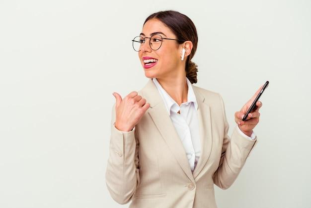 젊은 비즈니스 여자 엄지 손가락으로 멀리, 웃음과 평온한 흰 벽 포인트에 고립 된 휴대 전화를 들고.