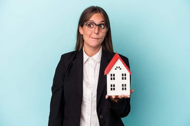 青い背景で隔離のおもちゃの家を保持している若いビジネス女性は混乱し、疑わしく、不安を感じています。