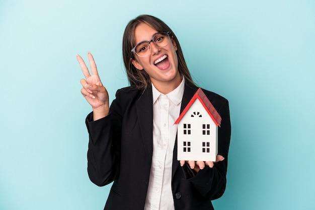 青い背景に隔離されたおもちゃの家を持っている若いビジネス女性は、指で平和のシンボルを示して楽しくてのんきです。