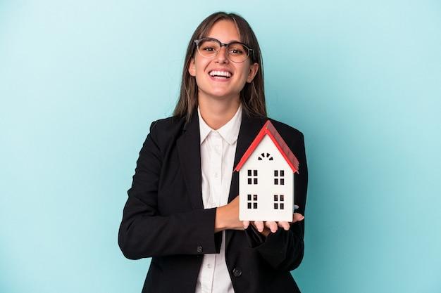 笑って楽しんで青い背景で隔離のおもちゃの家を保持している若いビジネス女性。