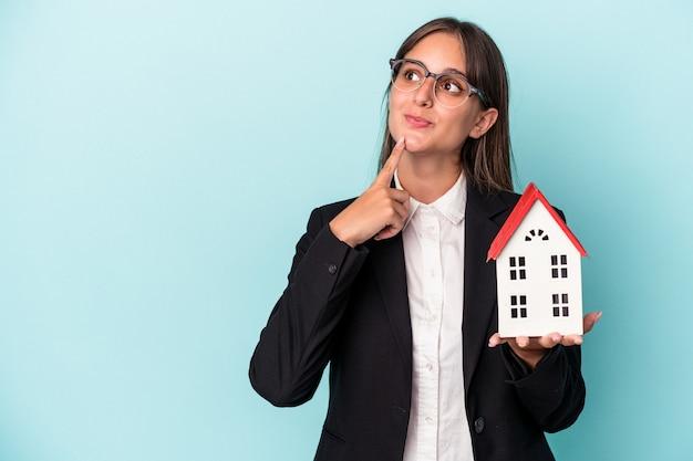 疑わしいと懐疑的な表情で横向きに青い背景で隔離のおもちゃの家を保持している若いビジネス女性。