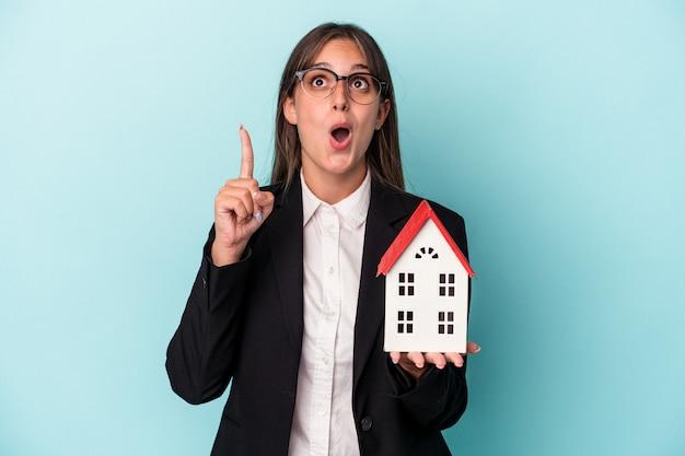 口を開けて逆さまを指している青い背景で隔離のおもちゃの家を保持している若いビジネス女性。