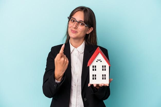 誘うようにあなたに指を指して青い背景で隔離のおもちゃの家を保持している若いビジネス女性が近づいています。