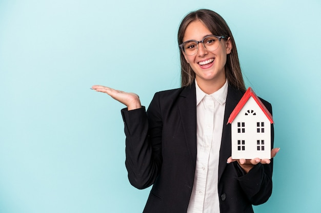 手のひらにコピースペースを示し、腰に別の手を保持している青い背景で隔離のおもちゃの家を保持している若いビジネス女性。