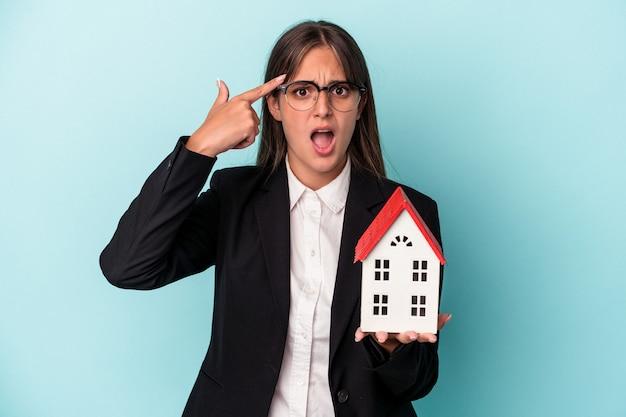 人差し指で失望のジェスチャーを示す青い背景で隔離のおもちゃの家を保持している若いビジネス女性。
