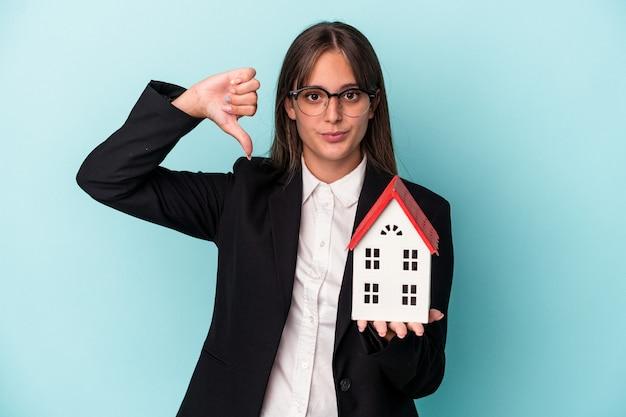 嫌いなジェスチャーを示す青い背景で隔離のおもちゃの家を保持している若いビジネス女性は、親指を下に向けます。不一致の概念。