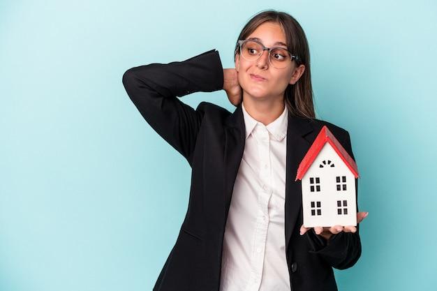頭の後ろに触れて、考えて、選択をする青い背景で隔離のおもちゃの家を保持している若いビジネス女性。