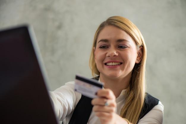 Молодая деловая женщина с кредитной карты и с помощью портативного компьютера. концепция онлайн-покупок. винтажные картины стиля эффекта.