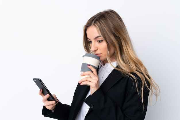 Young business woman holding a cup of coffee and a phone