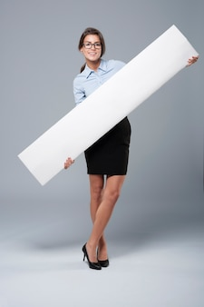 Young business woman holding the empty billboard
