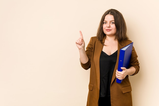 Young business woman holding files showing number one with finger