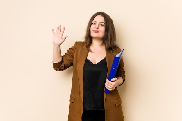 Молодая бизнес-леди, держащая файлы, улыбаясь, веселый показ номер пять с пальцами.