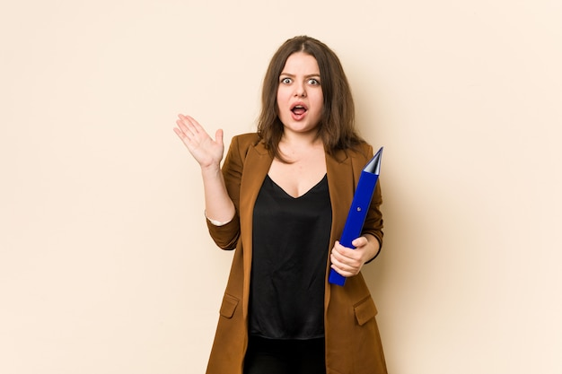 Young business woman holding files surprised and shocked.