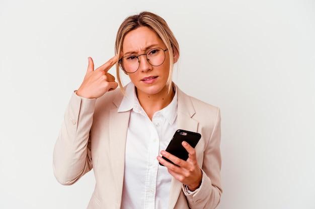 Молодая деловая женщина, держащая мобильный телефон, изолирована на белой стене, показывая жест разочарования указательным пальцем
