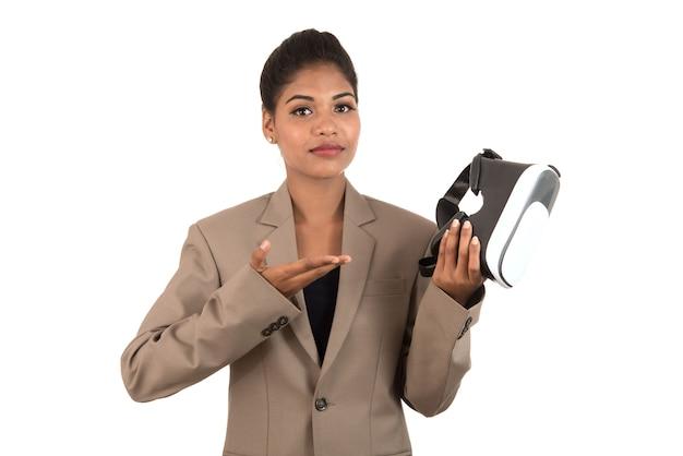 Молодая деловая женщина, держащая и показывающая устройство очки гарнитуры vr, изолированные на белом фоне