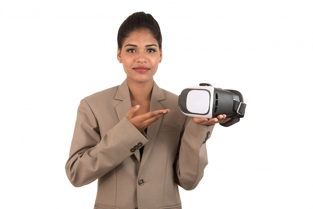 Young business woman holding & showing vr headset glasses device isolated on white wall