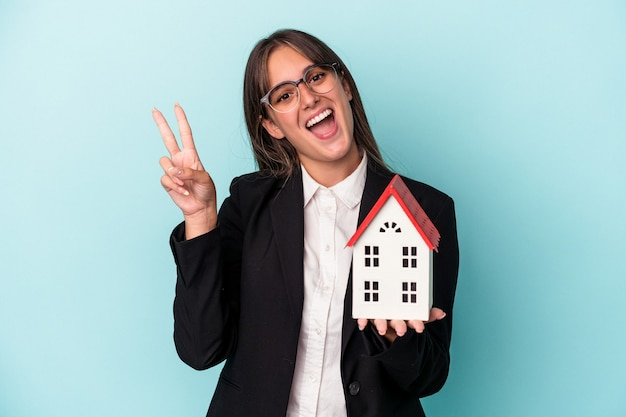 Young business woman holding a toy home isolated on blue background joyful and carefree showing a peace symbol with fingers.