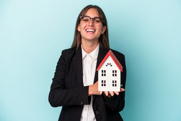 Young business woman holding a toy home isolated on blue background laughing and having fun.